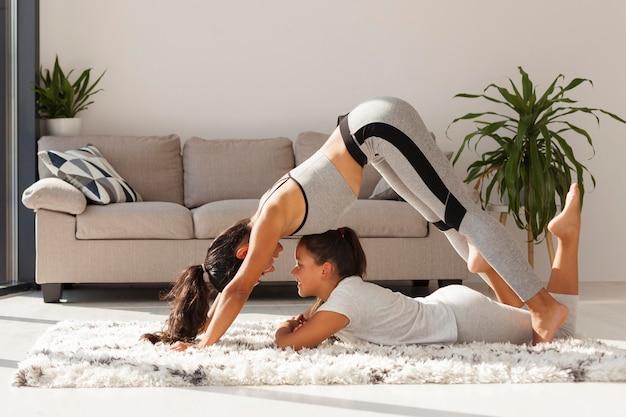 Mulher e menina praticando esportes dentro de casa