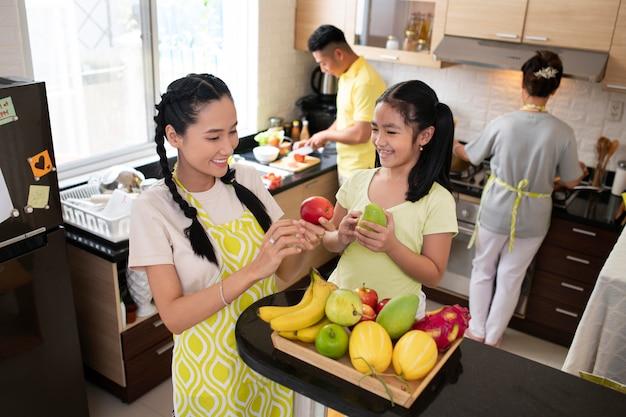 Mulher e menina segurando frutas