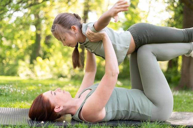 Mulher e menina treinando juntas, tiro completo