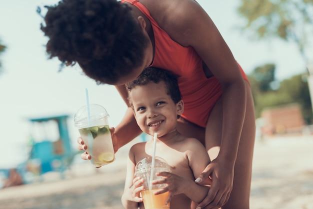 Mulher e menino está bebendo frio dia ensolarado de cocktails