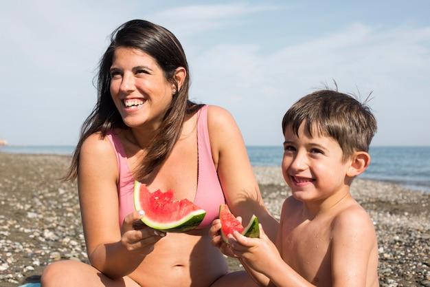 Mulher e menino próximos comendo melancia
