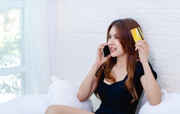 Mulher e mulheres de negócios de cartão de crédito falam ao telefone e olham para a ideia de negócio de cartão de crédito
