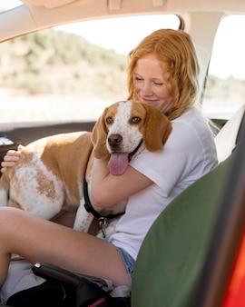Mulher e o cachorro dela sentados no carro