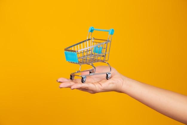 Mulher e o supermercado, ela está mostrando um mini carrinho. conceito de promoção de compras.