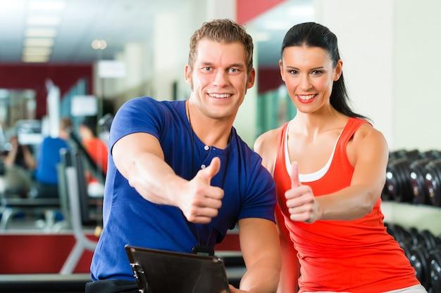 Mulher e personal trainer na academia com halteres