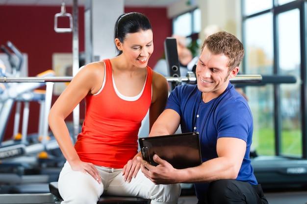 Mulher e personal trainer no ginásio de fitness