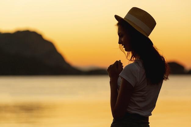 Mulher e pôr do sol na margem de um lago