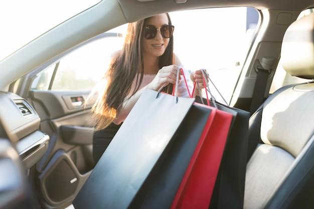Mulher e sacolas de compras no carro