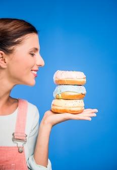 Mulher, é, segurando, donuts, ficar