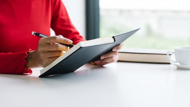 Mulher e segurando um livro e uma caneta, lendo algo com uma xícara de café, sentado na sala.