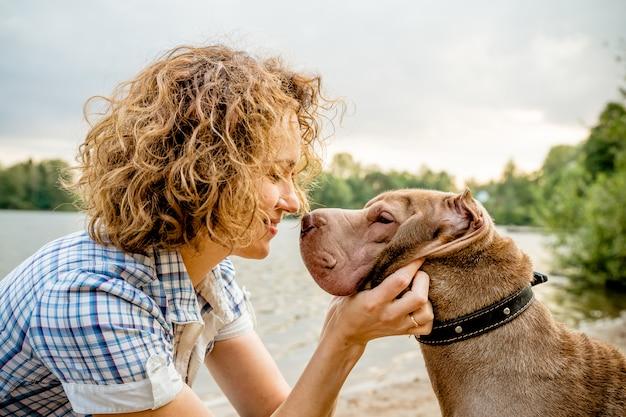 Mulher e seu animal de estimação, abraçando, beijando. amizade entre homem e cão