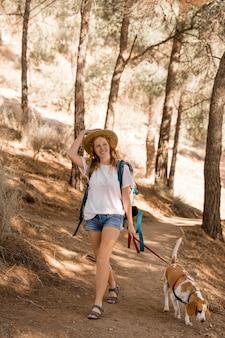 Mulher e seu cachorro andando na floresta à luz do dia
