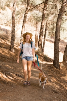 Mulher e seu cachorro andando na floresta de longa vista