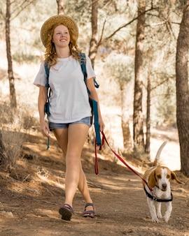 Mulher e seu cachorro andando na floresta