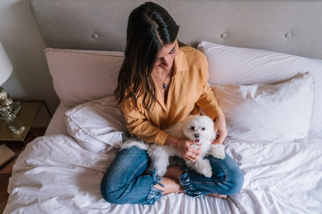 Mulher e seu cachorro fofo em casa bebendo chá