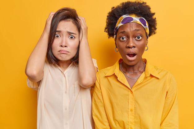 Mulher e sua amiga olham com expressão de pânico e medo percebem um grande problema ficarem um ao lado do outro isolado no amarelo