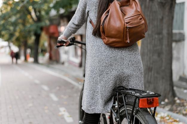 Mulher e sua bicicleta atirada por trás