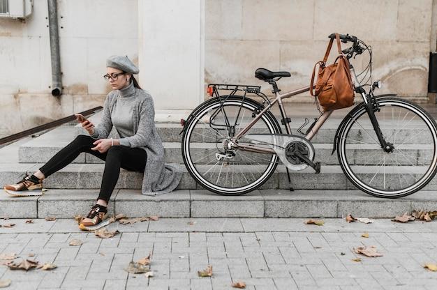 Mulher e sua bicicleta sentadas na escada