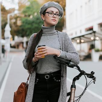 Mulher e sua bicicleta tomando café