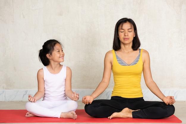 Mulher e sua encantadora filha fazendo meditação