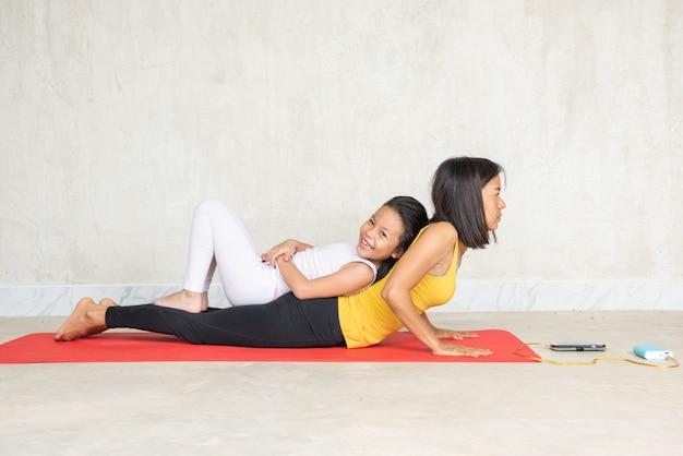 Mulher e sua encantadora filha fazendo yoga