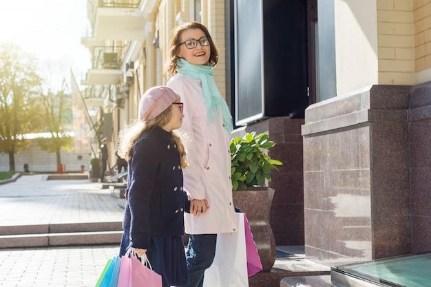 Mulher e sua filha pequena, com sacolas de compras andando pela rua
