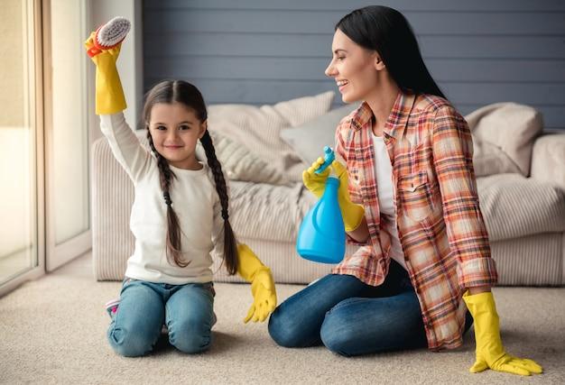 Mulher e sua filha pequena em luvas de proteção