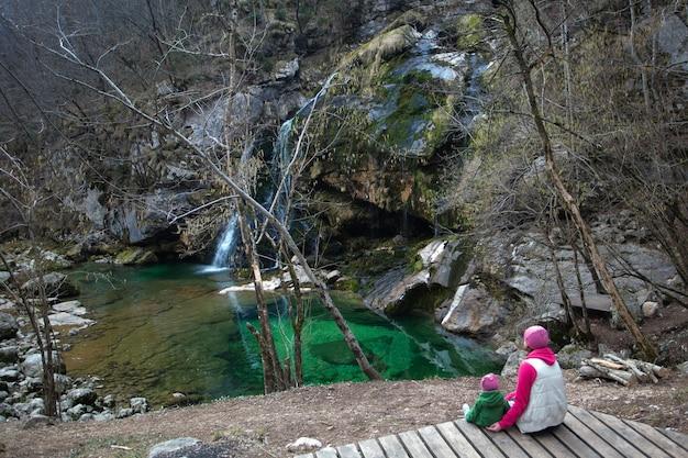 Mulher e sua filha pequena relaxante perto da cachoeira.
