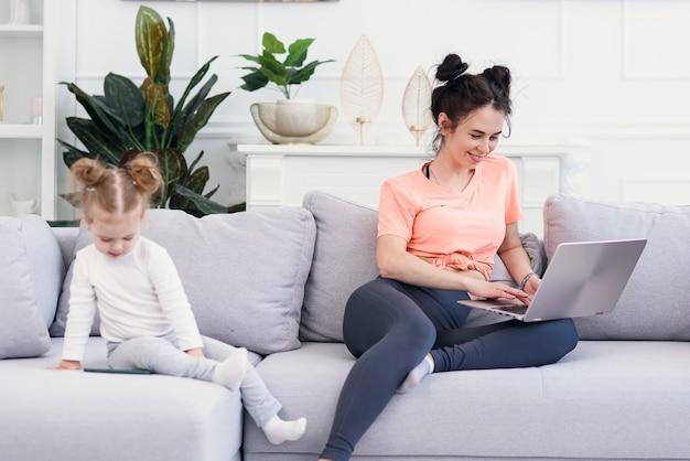 Mulher e sua filhinha feliz usando um laptop em casa