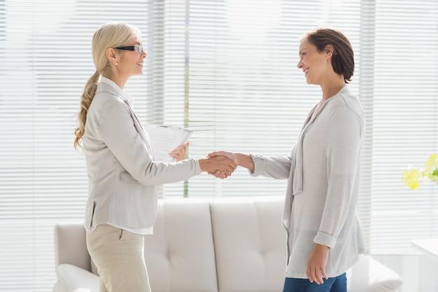 Mulher e terapeuta, apertando as mãos