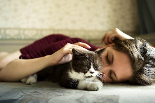 Mulher e um pequeno gatinho britânico preto e branco estão deitados no sofá