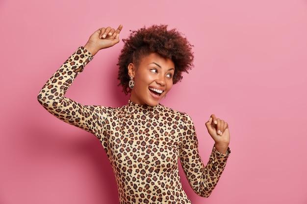 Mulher ecsatítica de pele escura e muito feliz com cabelo encaracolado, mantém as mãos levantadas, dança despreocupada, comemora vitória ou sucesso, usa gola alta de leopardo
