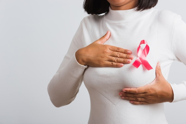 Mulher, ela tem uma fita rosa contra o câncer de mama no peito, ela segura o peito com a mão