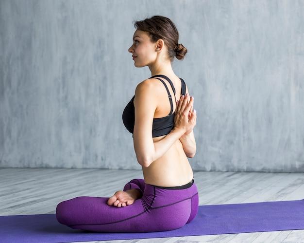 Mulher elástica, executar, um, namaste, ioga posa, atrás de, dela, costas