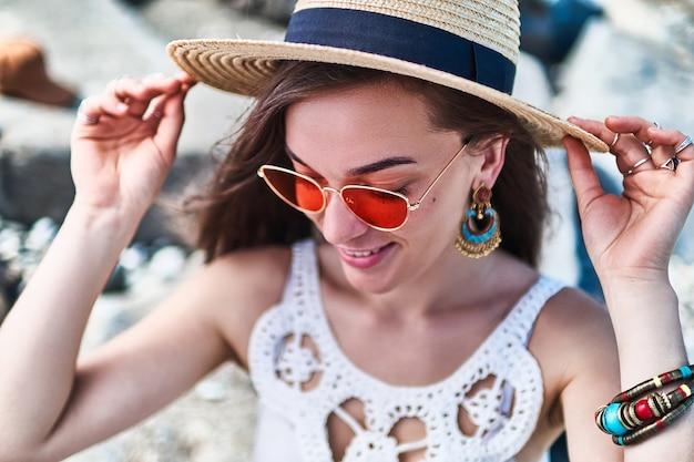 Mulher elegante alegre lindo verão brilhante em um chapéu de palha e óculos de sol vermelhos, vestindo uma blusa branca