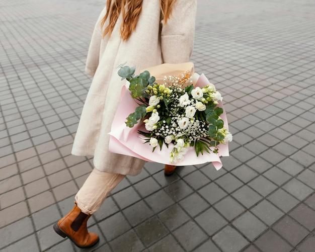 Mulher elegante andando pela cidade segurando buquê de flores