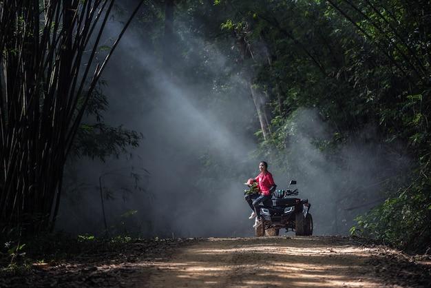 Mulher elegante, andar de quadriciclos atv na floresta