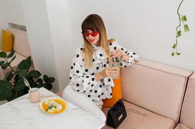 Mulher elegante blusa elegante e óculos vermelhos, aproveitando o fim de semana no café