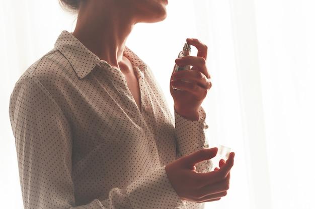Mulher elegante blusa pulverizando um frasco de perfume favorito fechar em casa.