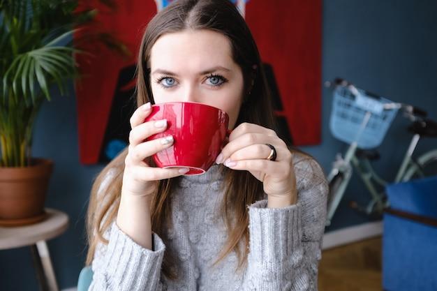 Mulher elegante bonita nova que senta-se em um café, guardando um copo do cappuccino, olhando a câmera, apreciando, rua da cidade, jantar romântico, ensolarada. menina tomando café. café da manhã. coffee break.