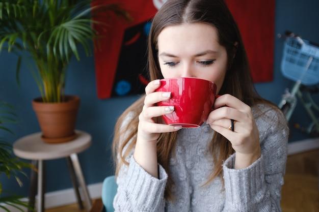 Mulher elegante bonita nova que senta-se em um café, guardando um copo do cappuccino, olhando para baixo, apreciando, rua da cidade, jantar romântico, ensolarada. menina tomando café. café da manhã. coffee break. aquece.