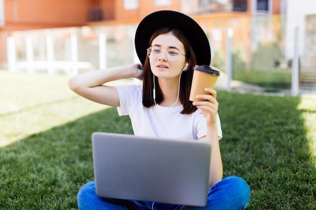 Mulher elegante bonita sentada na grama verde com laptop e café na mão. conceito de estilo de vida