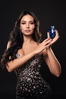 Mulher elegante bronzeada em um lindo vestido com perfume
