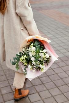 Mulher elegante caminhando ao ar livre e segurando um buquê de flores