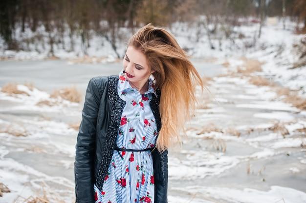 Mulher elegante casaco de cabedal em dia de inverno contra lago congelado.