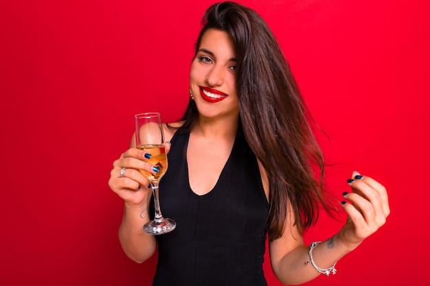 Mulher elegante caucasiana bonita com lábios vermelhos e longos cabelos escuros brincando, olhando para a câmera e bebendo champanhe.