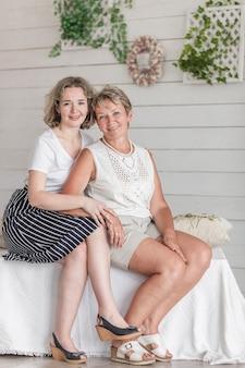 Mulher elegante com a mãe sentada no sofá olhando para a câmera
