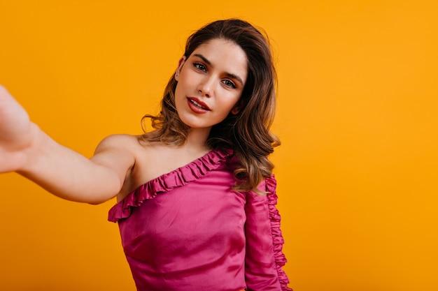 Mulher elegante com blusa rosa fazendo selfie