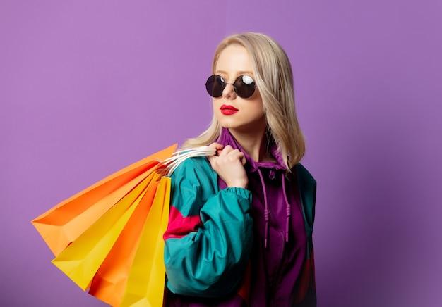 Mulher elegante com blusão de blusão dos anos 80 e óculos escuros com sacolas de compras na parede roxa