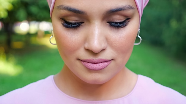 Mulher elegante com brincos de prata e hijab roxo com olhos fechados em frente ao close-up borrado do parque